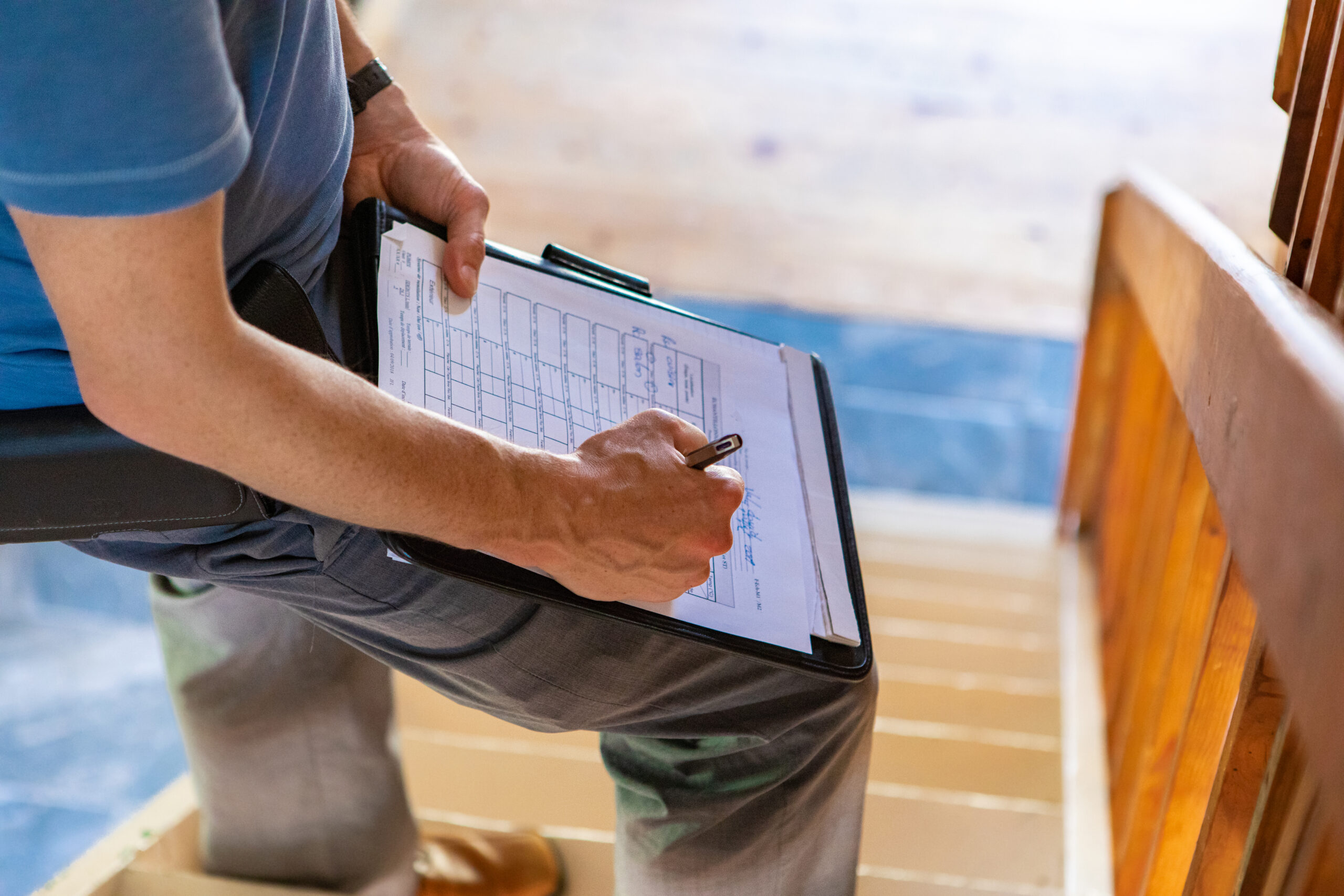 A close up and high angle view of a professional male wearing blue t-shirt, writing out forms during a home inspection, standing on stairs with copy-space.